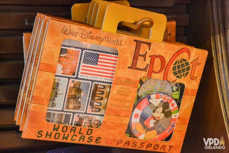 O passaporte do Epcot é uma lembrança super legal! Foto do passaporte do Epcot, com várias bandeiras de países na capa e um pin do Mickey na embalagem