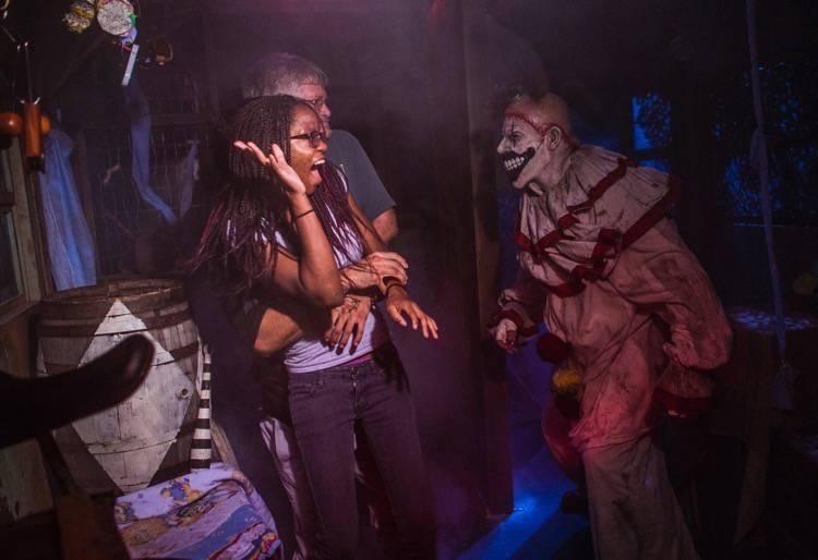 A imagem mostra dois visitantes sendo assustados por um palhaço assustador.