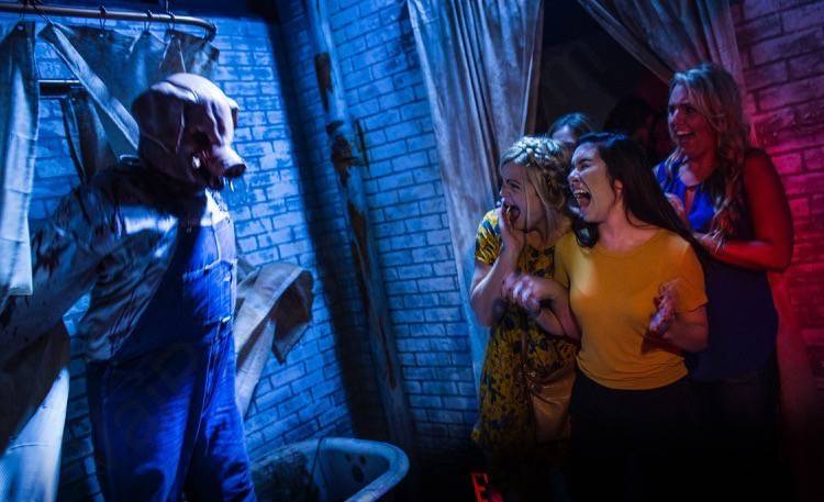 Foto da Halloween Horror Nights da Universal, uma das festas mais famosas de Orlando. A imagem mostra três visitantes gritando, após levarem um susto com um personagem com máscara de porco.