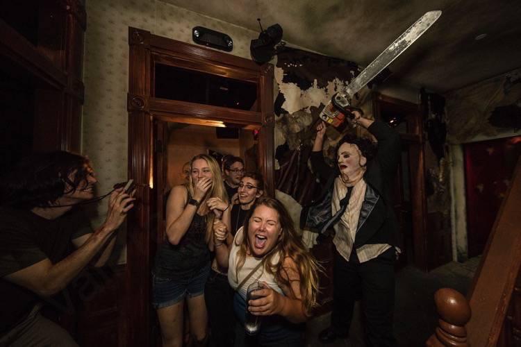 Foto da festa de Halloween da Universal. que mostra visitantes sendo assustados pelo personagem Leatherface, do Massacre da Serra Elétrica.