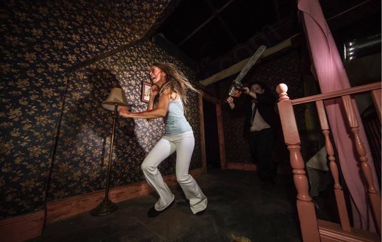 A imagem mostra uma moça assustada no corredor de uma casa, correndo de um personagem com uma motosserra.