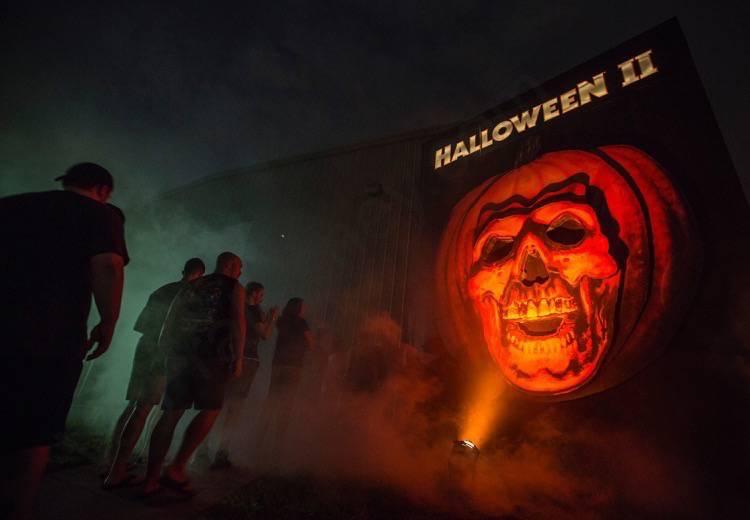 Labirinto do filme Halloween 2 na Halloween Horror Nights da Universal. A entrada mostra uma abóbora gigante com rosto de caveira, e visitantes enfileirados na porta.
