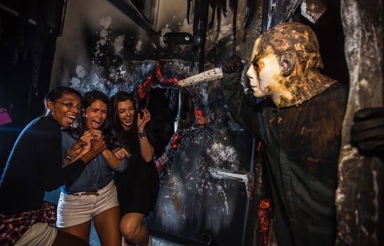 Halloween Horror Nights da Universal. A imagem mostra três visitantes levando um susto com uma pessoa vestida de Michael Myers, personagem de Halloween, com uma faca na mão.