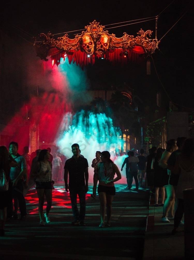 Festa Halloween Horror Nights. A imagem mostra a decoração de caveiras no teto, luzes coloridas e visitantes passando.