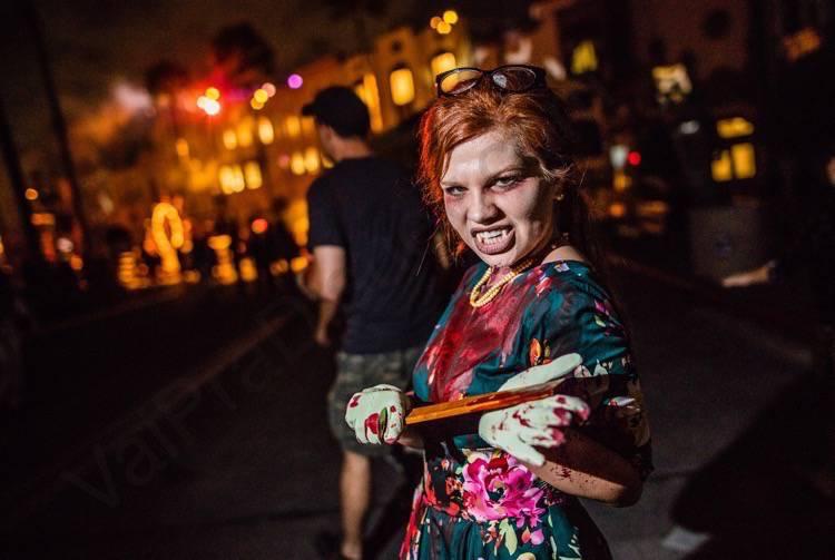 Halloween Horror Nights da Universal. Imagem de uma personagem com a roupa coberta de sangue, com um pedaço afiado de madeira nas mãos e dentes de vampiro.
