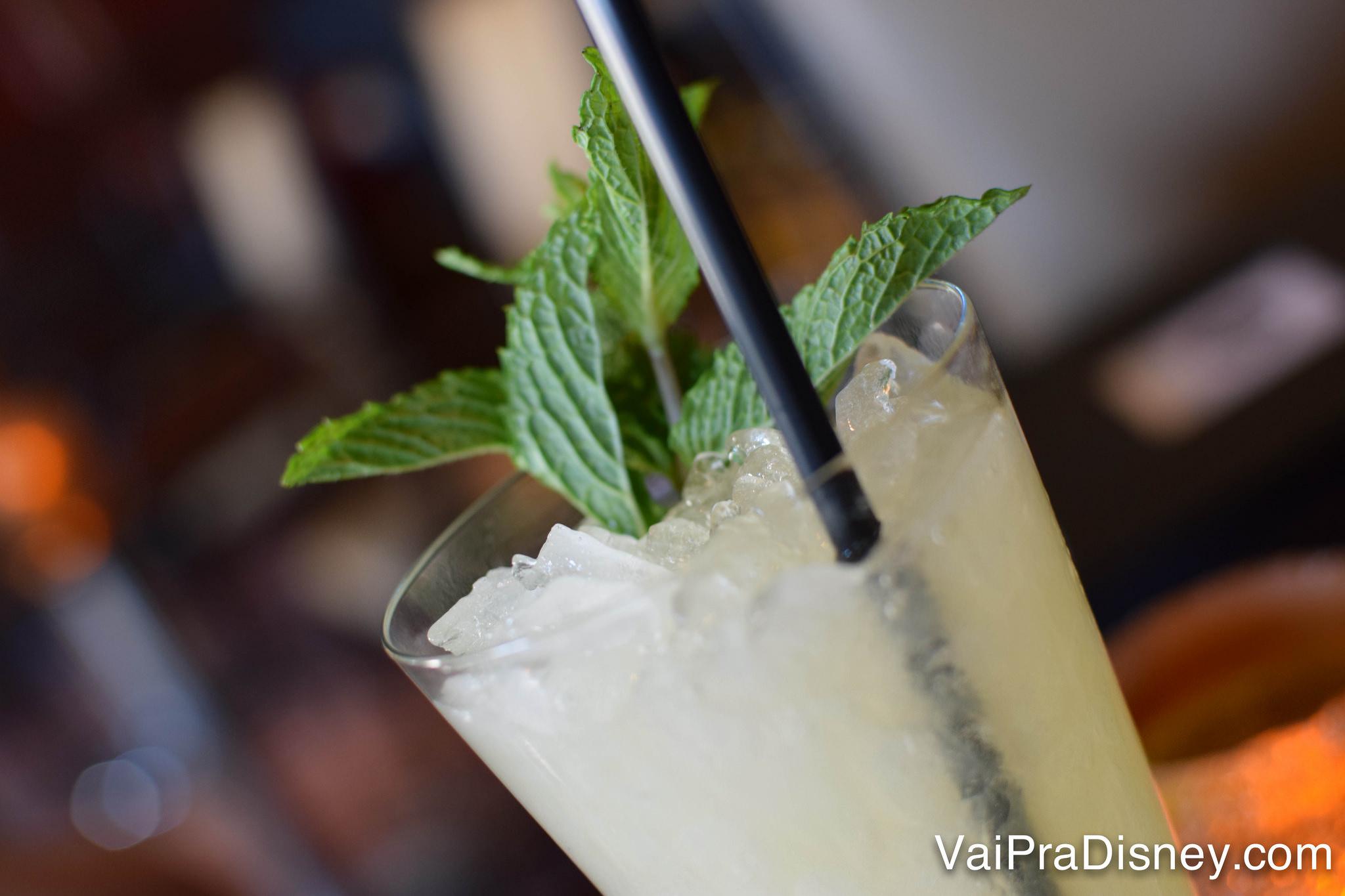 Foto de um drinque com canudo e hortelã em cima, servido em um copo comprido