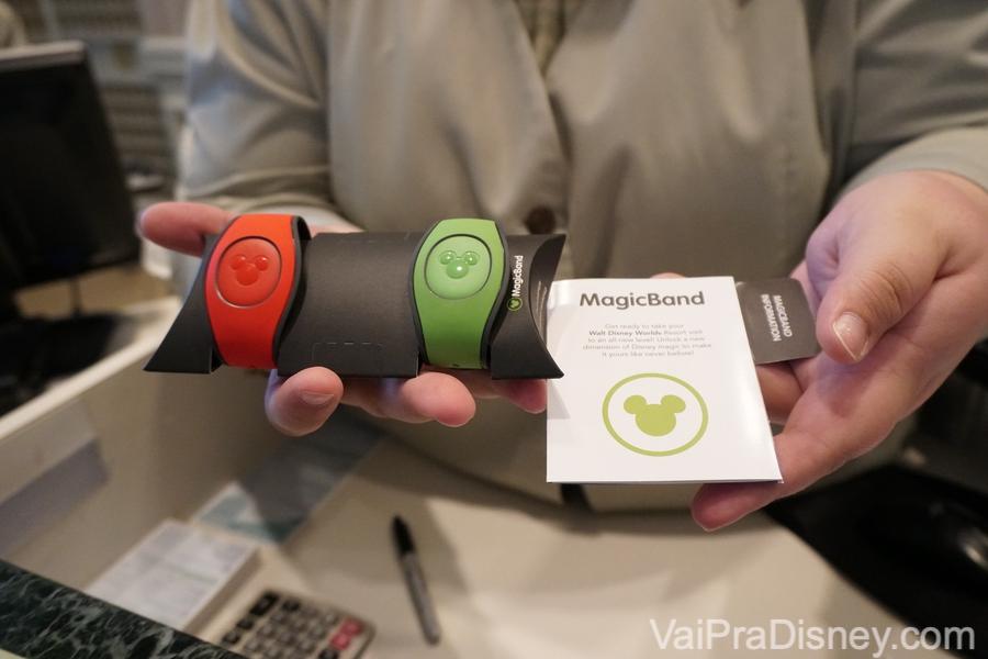 Todos os hóspedes de hotéis da Disney recebem as MagicBands no check in. Foto de uma mão segurando duas MagicBands dos hotéis da Disney, uma laranja e outra verde.