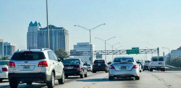 Foto da rodovia em Orlando, com diversos carros à frente e o céu claro ao fundo.