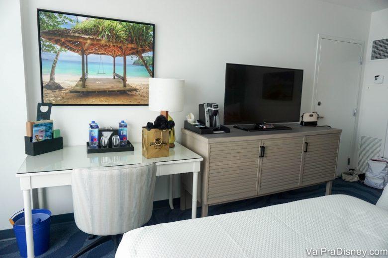 Foto do quarto mostrando um quadro de praia, uma escrivaninha e um móvel com tv em cima