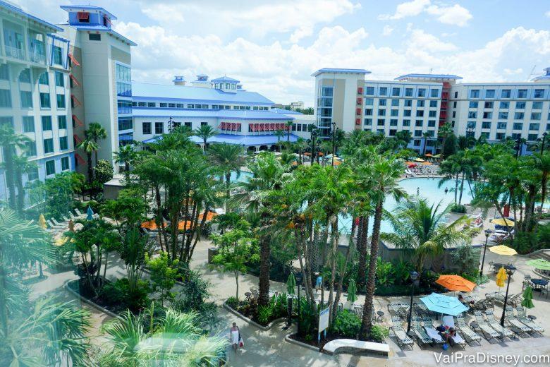 Foto da área externa do Loews Sapphire Falls Resort, mostrando o prédio branco com detalhes em azul e parte da área da piscina, com palmeiras em volta