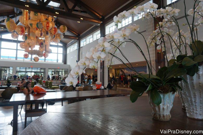 Outra foto do lobby mostrando flores sobre a mesa e o lustre de bolas de praia