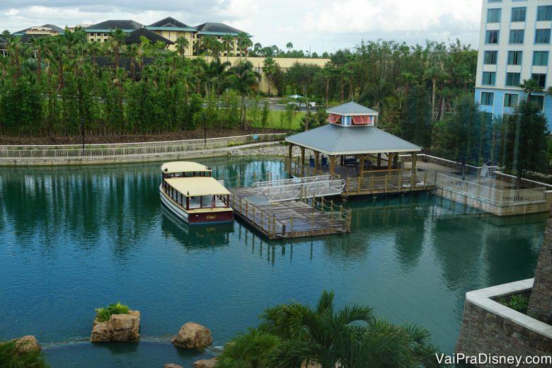 Foto do lago que fica no entorno do hotel, com um píer e um barquinho