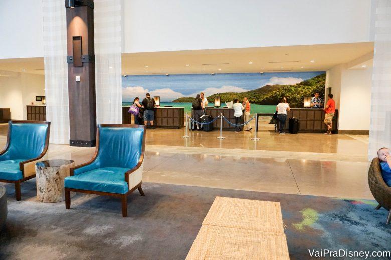 Foto da área da recepção do hotel, com cadeiras azuis e o balcão ao fundo
