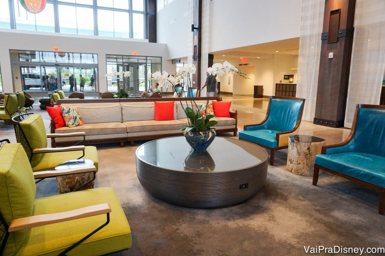 Foto da área da recepção do hotel, com cadeiras azuis e amarelas