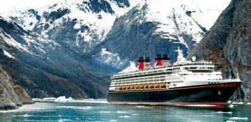 Foto do navio do cruzeiro da Disney com a geleira do Alaska ao fundo, em meio às montanhas, com o mar bem azul e o céu claro