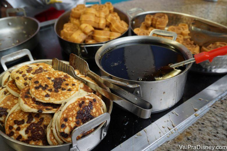 Foto de panquecas com gotas de chocolate, xarope de maple e waffles do Mickey no buffet