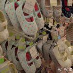 Foto de diversos sapatinhos de bebê à venda em uma loja, em sua maioria em cores claras.