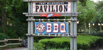 Foto da placa na entrada do Mickey's Backyard BBQ no Fort Wilderness, com fundo azul e um Mickey no centro