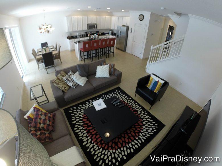 Outro ângulo da casa para poder dar noção do espaço. Foto de uma sala de estar com cozinha e sala de jantar ao fundo. A sala tem sofás cinzas, tapete e mesa de centro.