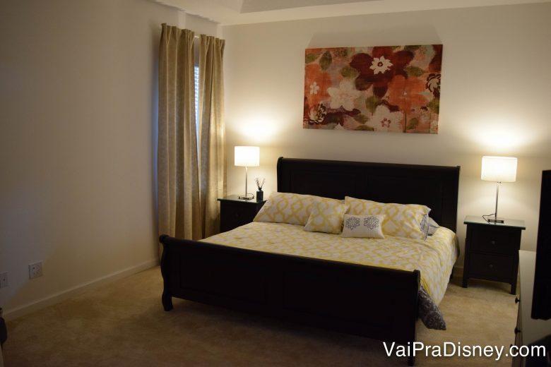 Um pouco do quarto principal da nossa casa. Foto da cama de casal no quarto principal da casa alugada, com lençóis amarelos e brancos e um quarto de flores na parede