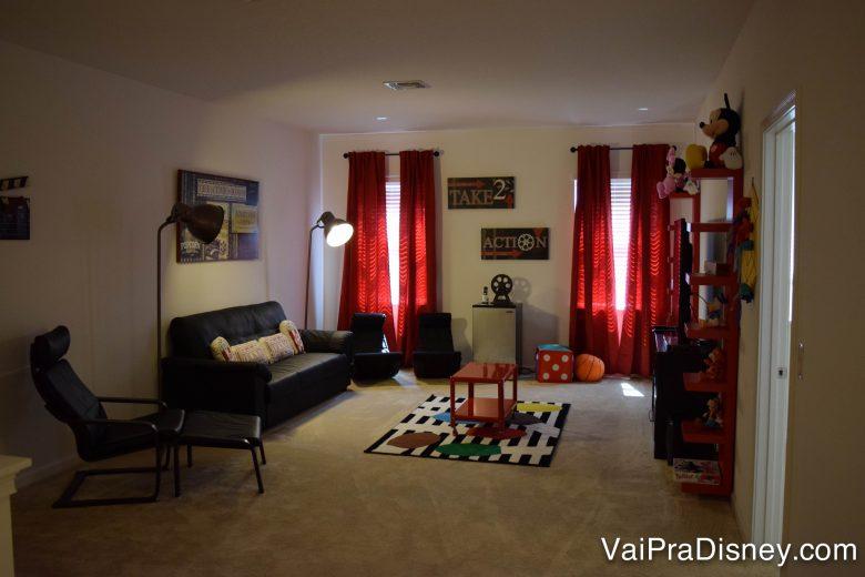 Salinha de TV no segundo andar da casa. Foto da sala de TV na casa alugada, com um sofá preto, uma poltrona preta e cortinas vermelhas.