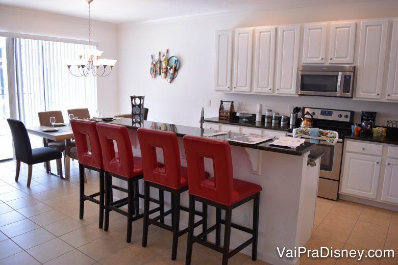 Cozinha completa para evitar fugir da rotina. Foto da cozinha de uma casa, com armários brancos e 4 cadeiras de espaldar vermelho.