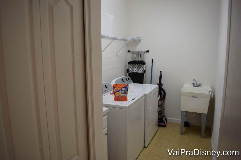 Lavanderia da casa. Foto da lavanderia na casa alugada, com máquinas e paredes brancas e um pacote de sabão em pó sobre uma das máquinas.