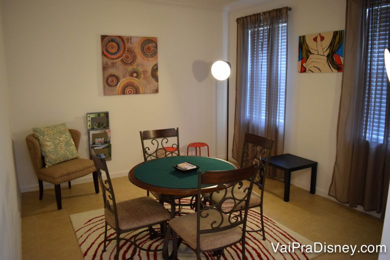 É normal ter até sala de jogos. Foto de uma sala de jogos de uma casa, com uma mesa central com 4 cadeiras.