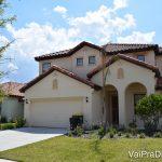 Foto de uma casa alugada em Orlando. Ela é pintada de cor clara, quase branca, tem um gramado verde à frente e o céu azul é visível atrás.