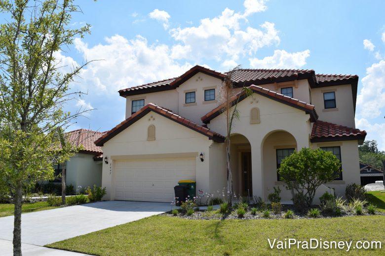 Entenda todo o sistema e protocolos de segurança da casa antes de alugar. Foto de uma casa alugada em Orlando. Ela é pintada de cor clara, quase branca, tem um gramado verde à frente.