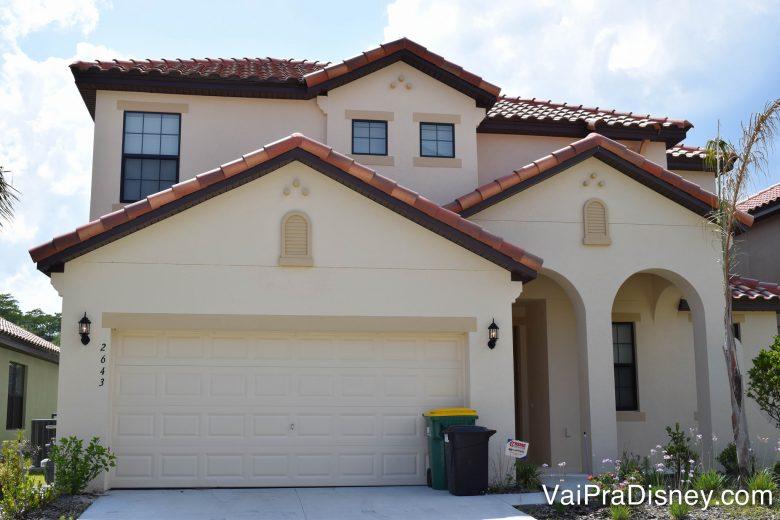 A casa que foi nossa durante certa viagem. :) Foto de uma casa alugada em Orlando. Ela é pintada de cor clara, quase branca, tem um gramado verde à frente e o céu azul é visível atrás.