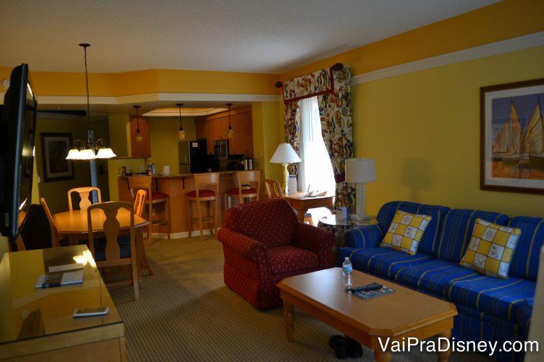 Um dos condos do Marriot que ficamos. Foto da sala de estar do condo, com um sofá azul, uma poltrona vermelha e a cozinha e sala de jantar mais ao fundo.