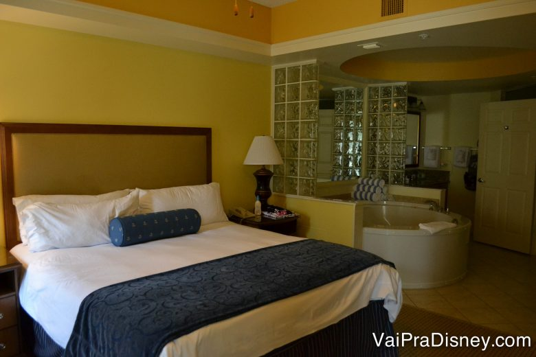 Também tem quartão nos apartamentos dos hotéis. Foto de um quarto em um condo, com uma cama de casal e uma banheira ao lado, separada por uma parede baixa.