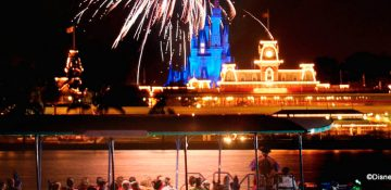 Foto dos fogos do Magic Kingdom, com o castelo e o parque iluminados ao fundo, tirada do barco do Pirates & Pals Fireworks Voyage