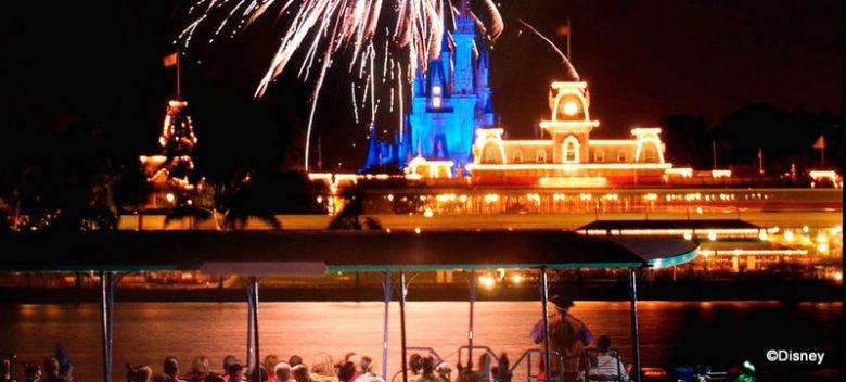 Foto do Magic Kingdom, com o castelo iluminado ao fundo e parte do lago e de um barco com visitantes visível em primeiro plano.