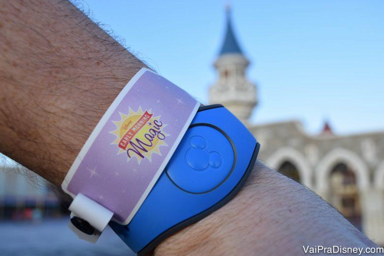Foto de uma mão com uma MagicBand azul no pulso e uma pulseira lilás identificando a pessoa como participante do Early Morning Magic. É possível ver o castelo da Cinderela ao fundo da foto.