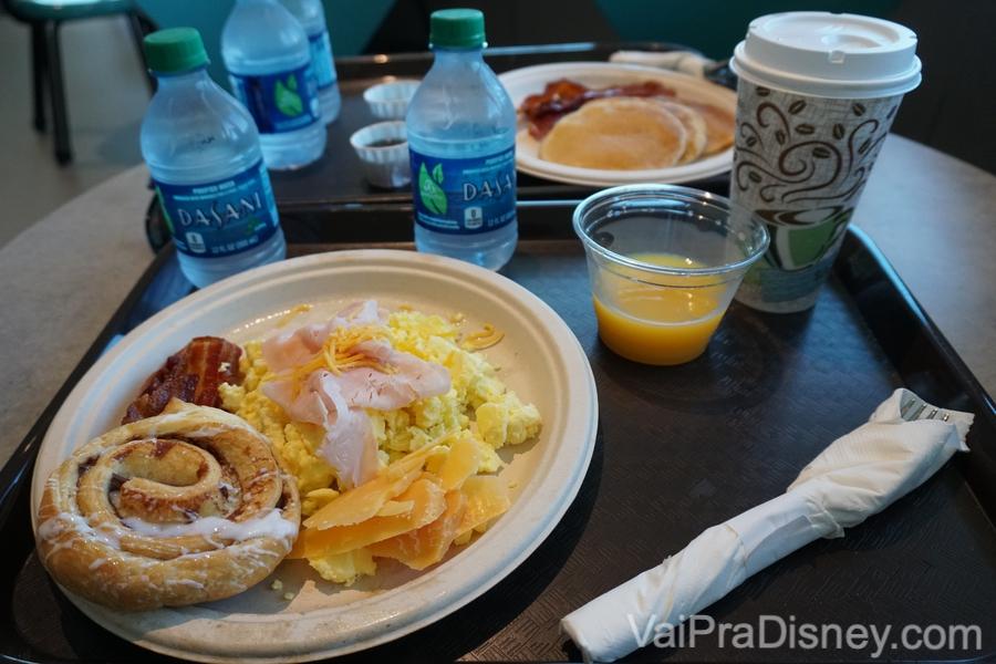 Foto do café-da-manhã servido no Early Morning Magic, com café, suco de laranja, água, ovos mexidos, pão doce e bacon.