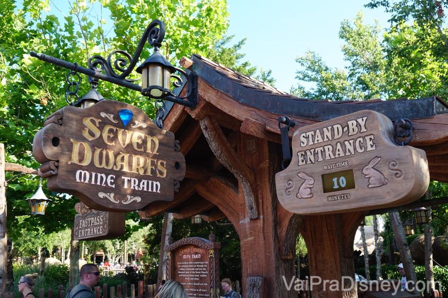 Foto das placas de madeira indicando a entrada da Seven Dwarfs Mine Train. O display digital mostra 10 minutos de fila sem Fastpass (stand-by entrance)