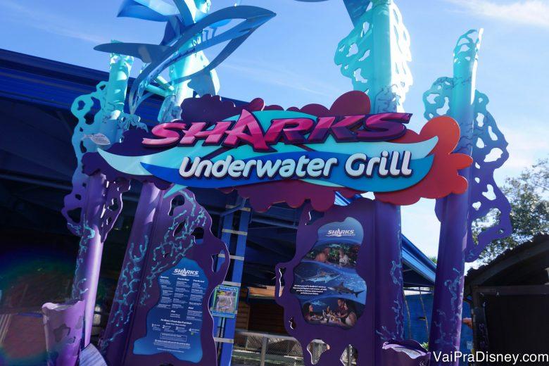 Foto da placa azul e rosa do Sharks Underwater Grill