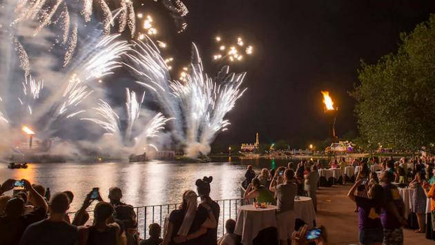 Foto da área VIP do IllumiNations Dessert Party, com várias mesas, e os fogos sobre o lago mais ao fundo da foto