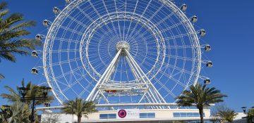 Foto da roda-gigante conhecida como The Wheel, em Orlando, com o céu azul ao fundo e a entrada do ICON Park em primeiro plano.