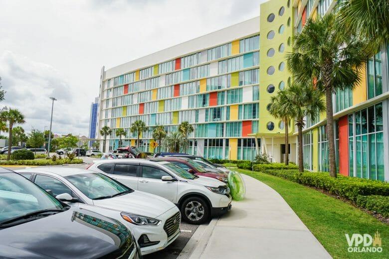 Muitos hotéis cobram uma diária para usar o estacionamento, como os da Disney e da Universal. Foto do estacionamento do Cabana Bay, com carros enfileirados e o prédio colorido ao fundo.