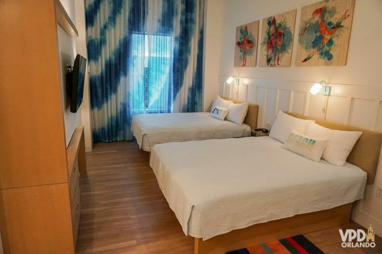 O Endless Summer tem quarto sem carpete! Foto do quarto do Endless Summer, com duas camas de casal, uma TV em frente, cortinas azuis e três quadros coloridos na parede.