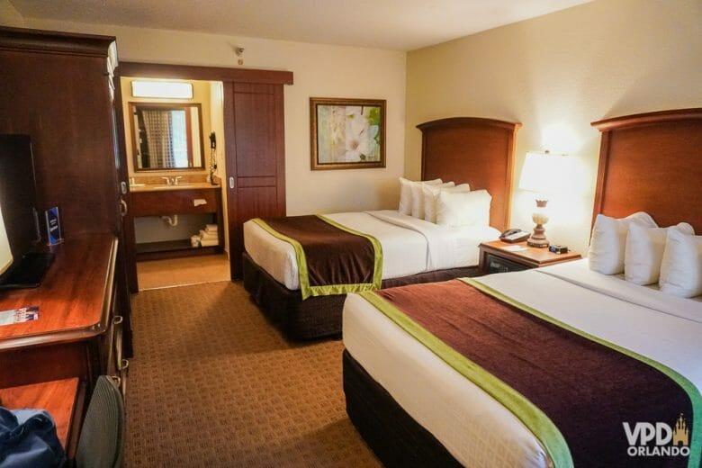 Um bom exemplo de hotel econômico e seguro em Orlando é o Clarion Inn Lake Buena Vista. Foto do quarto do Clarion Inn Lake Buena Vista, com duas camas de casal e a pia do banheiro à vista no fundo.