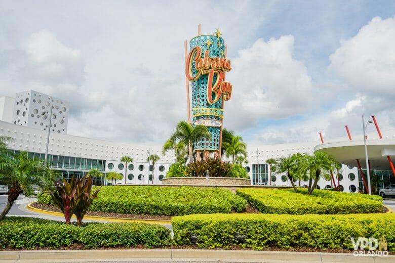 Entrada do hotel Cabana Bay, da Universal. Na foto é possível ver o totem central que tem o nome do hotel, letras laranjas em um fundo azul-turquesa.