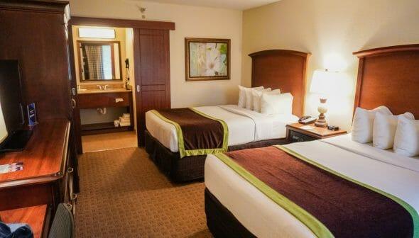 Foto do quarto do Clarion Inn Lake Buena Vista, com duas camas de casal e a pia do banheiro à vista no fundo.