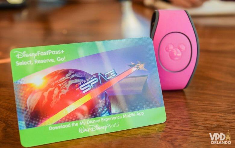 Os ingressos podem ser usados no cartão ou na MagicBand através do e-ticket. Imagem do cartão magnético que funciona como ingresso da Disney, ao lado de uma MagicBand cor-de-rosa.
