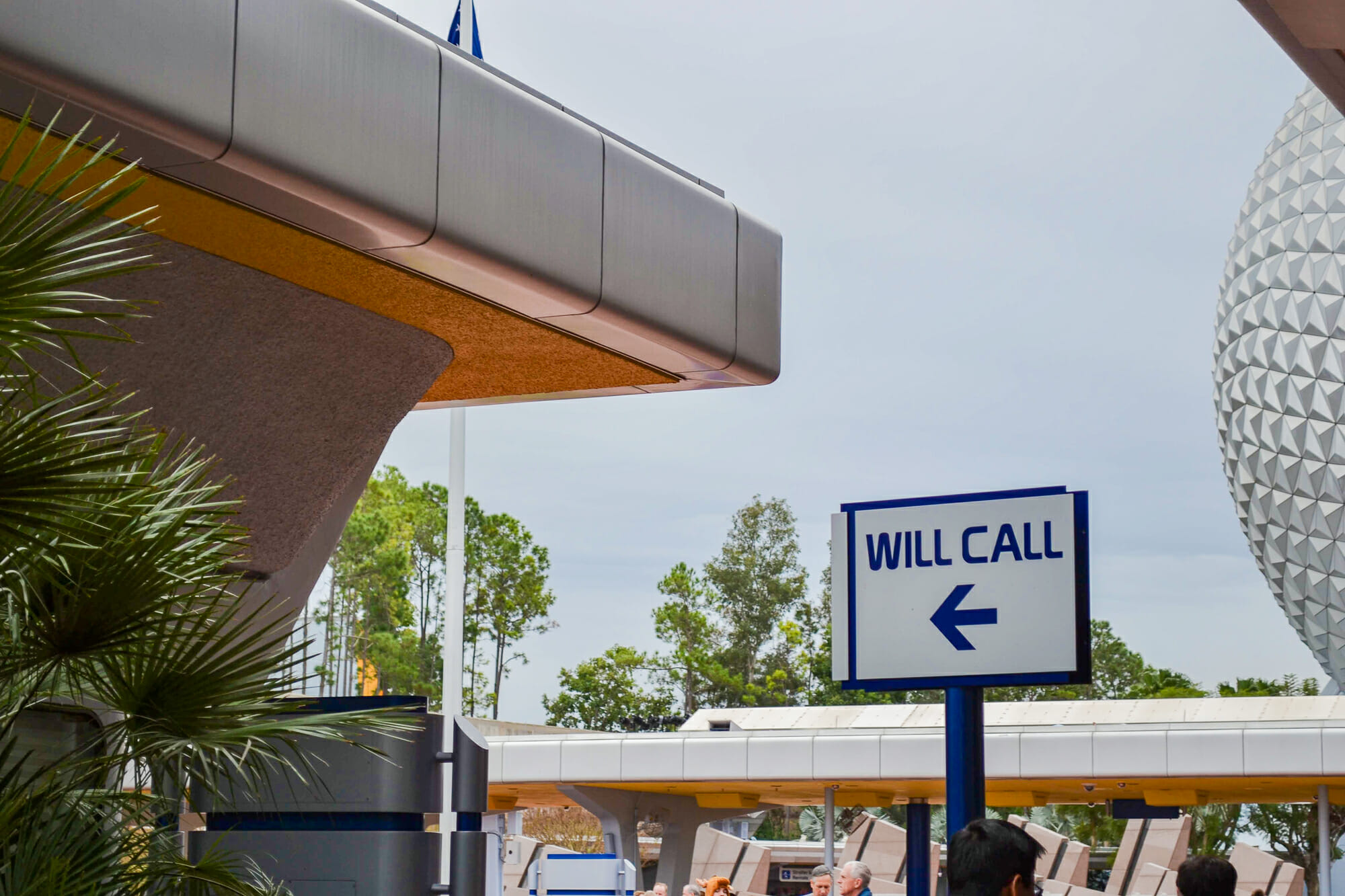 """Foto com a placa indicando a direção do Will Call no Epcot, com parte da """"bola"""" visível na lateral da imagem. A placa tem fundo branco, letras azuis, uma flecha apontando para a esquerda e diz """"Will Call"""""""
