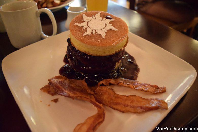 Foto de um torre de panquecas com blueberry e bacon ao redor.