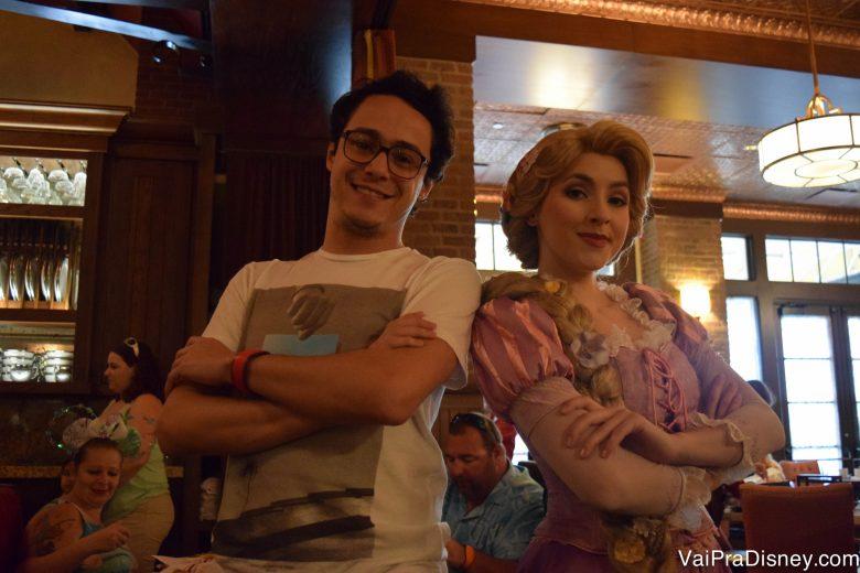 Foto do Henrique ao lado da Rapunzel, ambos posando de braços cruzados, no Bon Voyage Breakfast da Trattoria al Forno